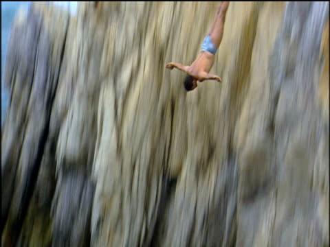 Quebrada cliff diver leaps from rock face into sea Mexico