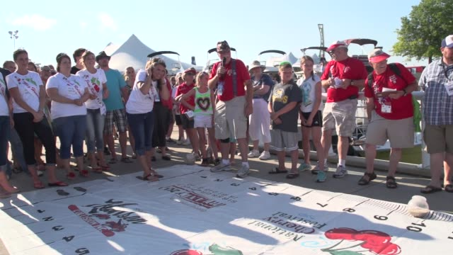 vidéos et rushes de queen and court of national cherry festival takes turn at cherry spitting contest - traverse city