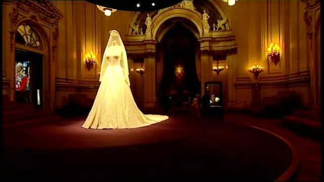 queen and duchess of cambridge visit wedding dress exhibition at buckingham palace; wedding dress on display with queen and catherine walking past in... - curator stock videos & royalty-free footage