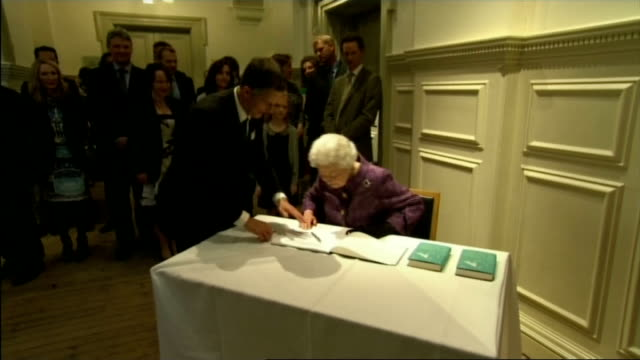 queen and duke of edinburgh at royal geographical society close shots of queen chatting to guests / queen signing visitors' book / queen presented... - book signing stock videos & royalty-free footage