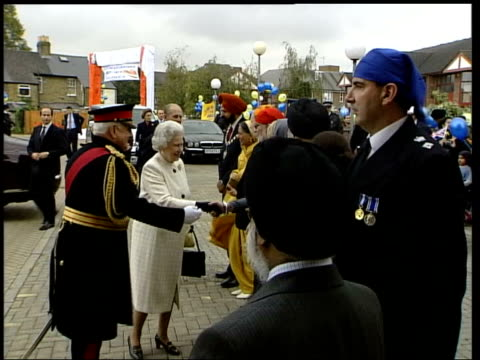 queen and duke of edinburgh open sikh temple in hounslow england london ext women waiting with flowers outside temple to greet queen / ground to air... - official car stock videos & royalty-free footage