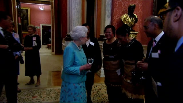 Queen and Prince Charles host Commonwealth reception Guests milling about during the reception / Queen talking to various people