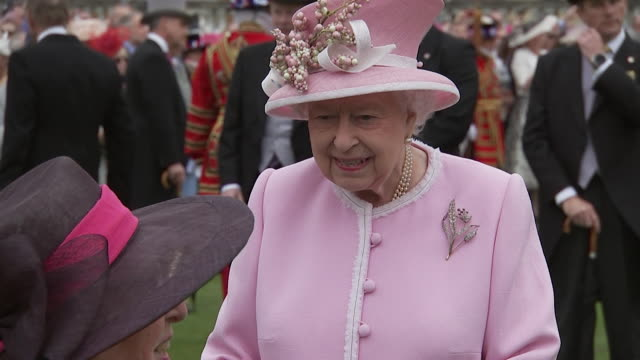 queen and prince harry attend royal garden party on rain day in grounds of buckingham palace - königin elisabeth ii. von england stock-videos und b-roll-filmmaterial