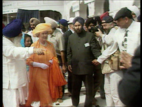 vídeos y material grabado en eventos de stock de queen and prince philip collection 3; t14109713 i india tour: nicholas owen piece to camera; amritsar: at golden temple; queen in ankle socks inside;... - social media