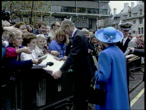 Golden wedding anniversary EXT Queen and Prince Philip walking along talking to crowd and receiving gifts and flowers and the Duke receives a large...