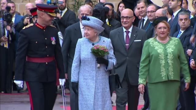 Queen arrives in Malta Queen along with flowers followed by Prince Philip / Queen stands atop small podium with Marie Louise Coleiro Preca and...
