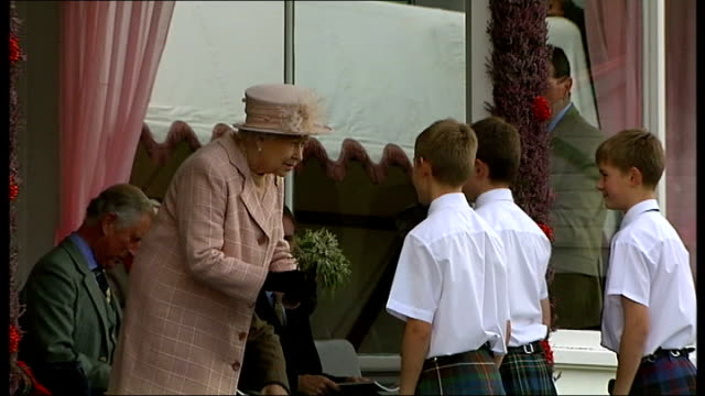 queen attends braemar highland games triplets presenting queen with heather posey / high angle highland games including man tossing a caber - highland games stock videos & royalty-free footage