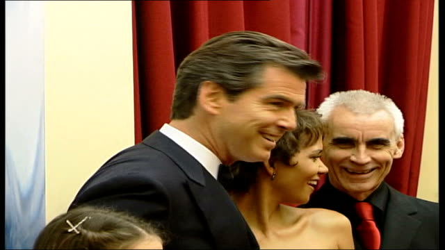 queen attends 'die another day' premiere at royal albert hall england london royal albert hall pierce brosnan walking along in room brosnan kissing... - pierce brosnan stock videos and b-roll footage