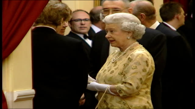 queen attends 'die another day' premiere at royal albert hall; england: london: royal albert hall: the queen & duke along shaking hands with various... - film premiere stock videos & royalty-free footage