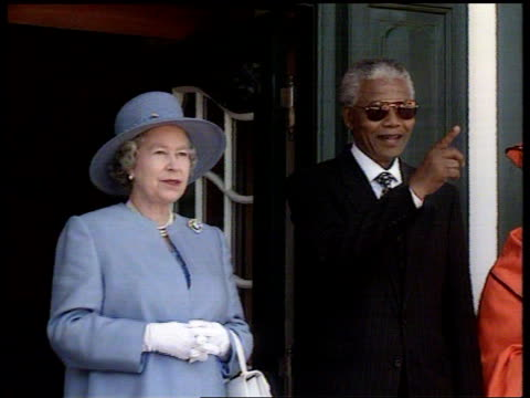 Queen attends parliament Meets Nelson Mandela LS Queen next Philip seated in back of car as along PAN LR TLS Car along CMS Queen next Mandela smile...