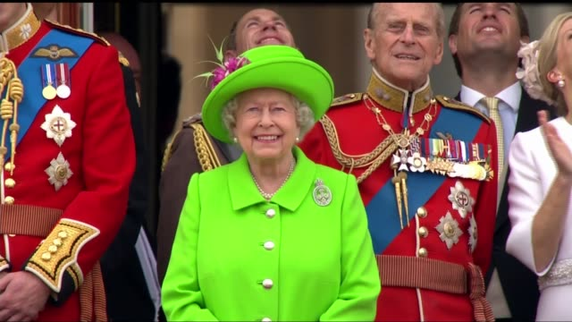 queen elizabeth 90th birthday: trooping the colour; queen elizabeth waving and smiling from buckingham palace balcony as watching red arrows fly-past... - 軍旗分列行進式点の映像素材/bロール