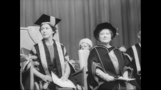 Queen Elizabeth and daughter Princess Margaret arrive at Keele University to honor Elizabeth with degree / inside university seated audience listen...