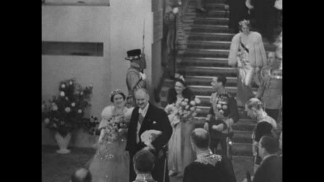 Queen Elizabeth and French President Albert Lebrun walk down staircase at Royal Opera House after a ballet performance King George VI escorts French...