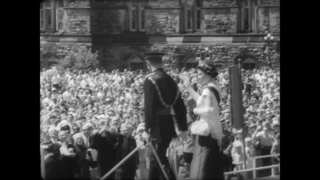 queen elizabeth and prince philip greet crowd at parliament hill in ottawa / huge crowd of children surround giant centennial cake / queen cuts cake... - parliament building stock videos & royalty-free footage