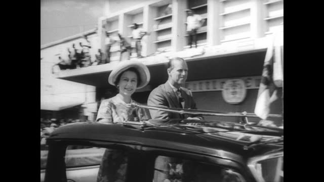 queen elizabeth and prince philip stand in the back of a car waving to crowd as they complete their caribbean tour - 1966 stock-videos und b-roll-filmmaterial