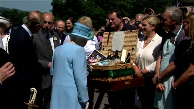 queen elizabeth and prince philip visit chatsworth house; england: derbyshire: chatsworth house: ext schoolchildren present queen elizabeth with... - 見渡す点の映像素材/bロール