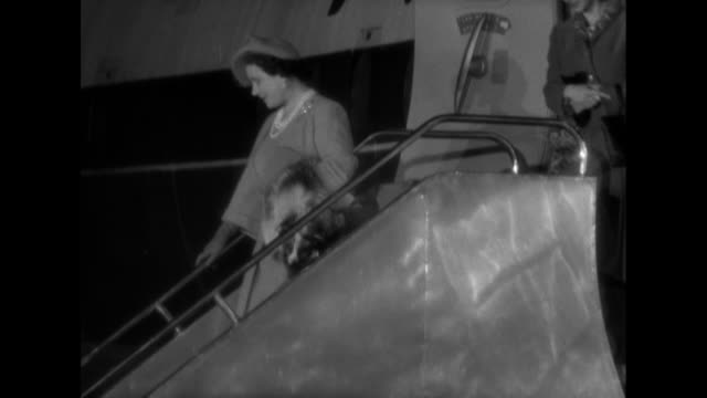 Queen Elizabeth and Princess Margaret leave an aircraft at London Airport