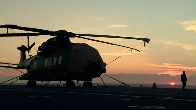 stockvideo's en b-roll-footage met hms queen elizabeth arrives in portsmouth english view from deck of hms queen elizabeth at sunrise silhouette of military aircraft on deck of ship... - het kanaal