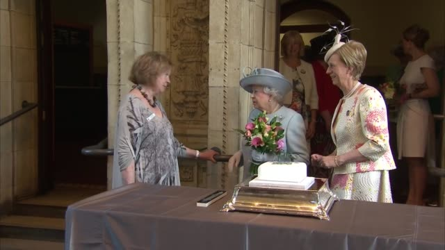 queen elizabeth attends women's institue centenary agm; queen into room and shakes hands and chats with guests / queen up to cake table / queen tries... - sophie rhys jones, countess of wessex stock videos & royalty-free footage