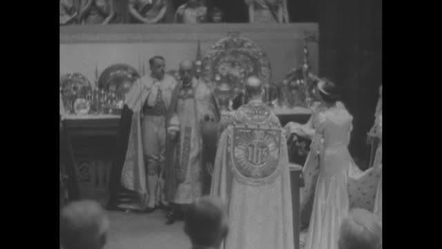 queen elizabeth enters westminster abbey maids of honor holding train of gown / queen stands before chair of estate / king enters abbey attendants... - coronation stock videos and b-roll footage