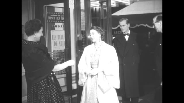 Queen Elizabeth II and husband Prince Philip enter lobby of theater and are greeted by Mme Odette Massigli wife of French Ambassador Rene Massigli as...