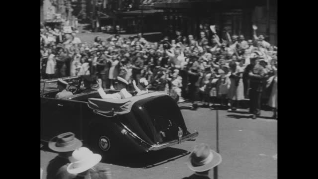 Queen Elizabeth II and Philip Duke of Edinburgh enter open limousine / high angle of motorcade driving underneath decorative arch with large crowd /...