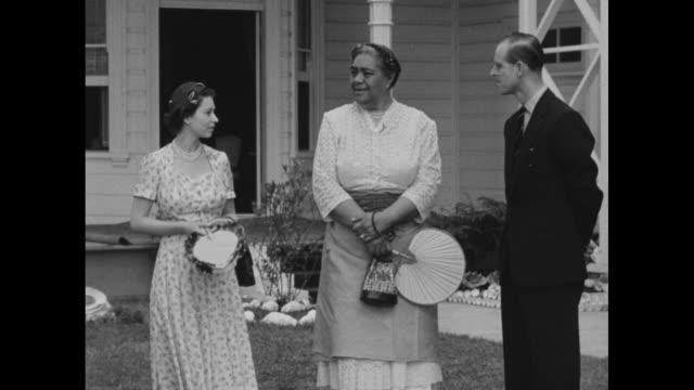 vídeos y material grabado en eventos de stock de queen elizabeth ii and prince philip, duke of edinburgh, with maori woman outside plantation-style structure during visit to new zealand / various... - visita de estado
