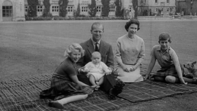 queen elizabeth ii and prince philip, duke of edinburgh with their children, baby prince andrew , princess anne and charles, prince of wales sitting... - タータンチェック点の映像素材/bロール