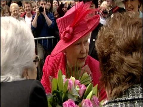 vídeos y material grabado en eventos de stock de queen elizabeth ii and prince philip on walkabout for queen's 80th birthday people in crowd give queen numerous bunches of flowers windsor 21 apr 06 - estilo del 2000