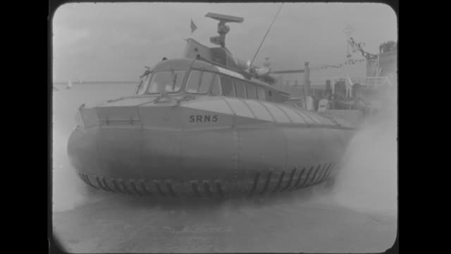queen elizabeth ii and prince philip ride in hovercraft; england: isle of wight: yarmouth: ext small boats in harbour quay with royal yacht britannia... - waterfront stock videos & royalty-free footage