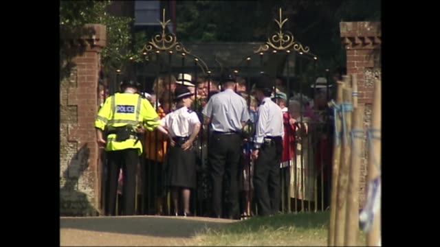 queen elizabeth ii and the queen mother attend church on sandringham estate; england: norfolk: sandringham estate: ext police opening gates and... - queen's birthday stock videos & royalty-free footage