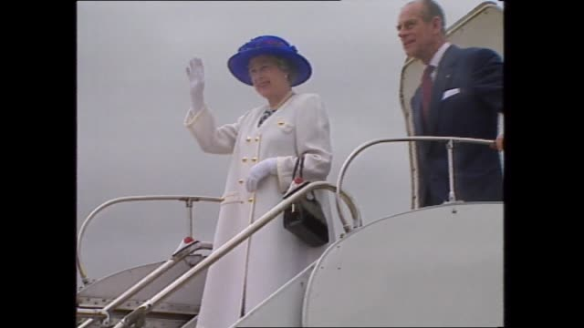 royal plane taxiing on tarmac alternating with shots of the royal standard flag / paul and annita keating walking / queen stands at plane door and... - queen royal person stock videos & royalty-free footage