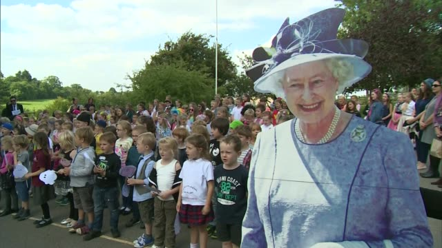 queen elizabeth ii becomes longest reigning monarch; england: kent: ext children singing the national anthem to a large cardboard cut-out of the... - 皇族・王族点の映像素材/bロール