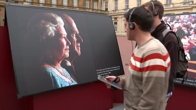 queen elizabeth ii becomes longest reigning monarch; people looking at photographs gordon interview continues sot cutaways people looking at... - 皇族・王族点の映像素材/bロール