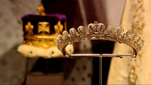 queen elizabeth ii coronation exhibition opens; buckingham palace: int royal tiara on display visitor walking past display - crown headwear stock videos & royalty-free footage