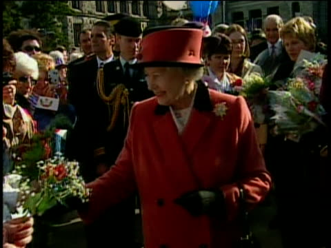 Queen Elizabeth II dressed in red suit and hat receives flowers from well wishers during walkabout for her jubilee tour 07 Oct 02