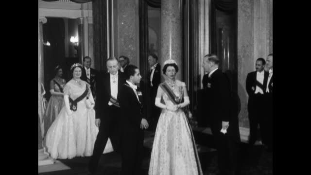 Queen Elizabeth II enters room with King Faisal II of Iraq / Elizabeth Faisal and others standing / Elizabeth and Faisal walking / Queen Mother...