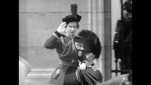/ Queen Elizabeth II exits palace on horse back in formal dress to a waiting crowd / aerial view of horse guard parade / Queen Mother and Princess...