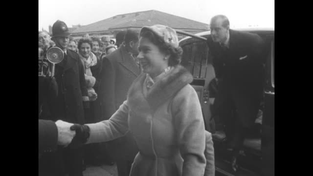 Queen Elizabeth II gets out of car followed by Prince Charles and Philip Duke of Edinburgh / shake hands with greeters continue into the stadium /...