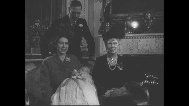 ms queen elizabeth ii holds infant prince charles in her lap queen mary seated beside her and king george vi behind them for portrait / cu queen mary... - coronation stock videos and b-roll footage