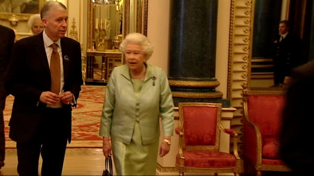 queen elizabeth ii hosts media reception at buckingham palace queen elizabeth chatting as takes lipstick from bag and applies it then puts lipstick... - borsetta video stock e b–roll