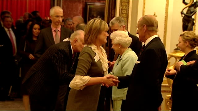 queen elizabeth ii hosts media reception at buckingham palace; queen elizabeth and prince philip greeting guests including mary nightingale and fiona... - エイモン ホームズ点の映像素材/bロール