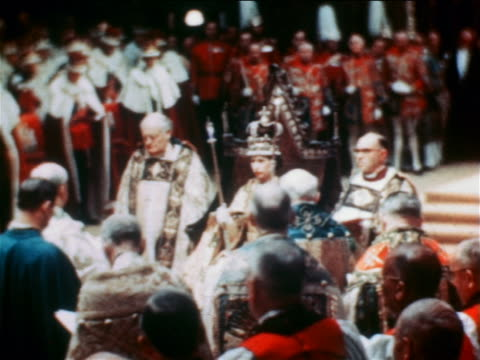 vídeos y material grabado en eventos de stock de queen elizabeth ii in crown sitting on throne surrounded by clergy in coronation ceremony - corona accesorio de cabeza