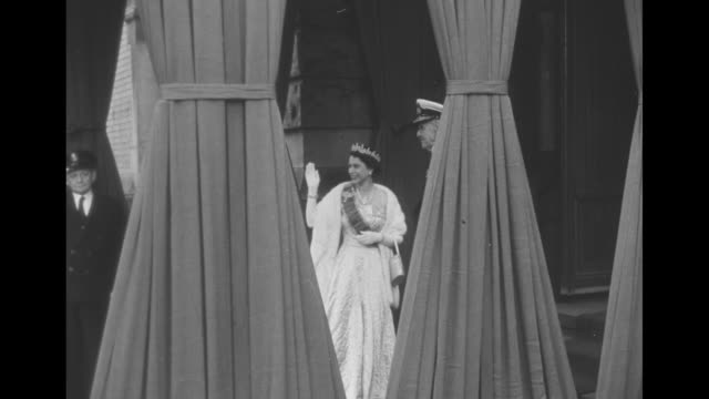 Queen Elizabeth II in evening gown and tiara waves as she walks with King Haakon VII during her visit to Norway / WS HMY Britannia in harbor dressed...