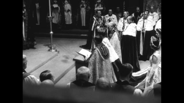 queen elizabeth ii kneels, places her fingers on the bible, kisses the bible, and signs the coronation oath - oath stock videos & royalty-free footage