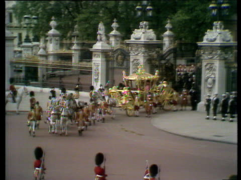 Queen Elizabeth II leaves Buckingham Palace in state carriage flanked by cavalry and royal attendants public crowds cheer enthusiastically Silver...