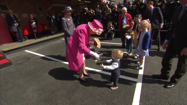 Queen Elizabeth II looking radiant in bright pink is treated to a rendition of 'Happy Birthday' by a choir formed by Royal Mail staff after her visit...