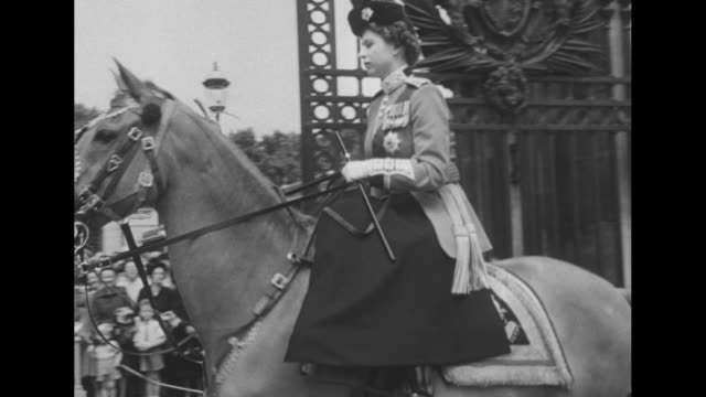 Queen Elizabeth II on horseback leaves the Trooping the Colour procession saluting the Guards as she goes through archway at Buckingham Palace /...