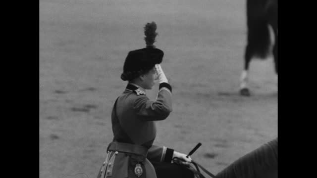 queen elizabeth ii passes saluting and riding on horseback in foreground as rear shot guards stand in background at trooping the colour ceremony at... - 1954 bildbanksvideor och videomaterial från bakom kulisserna