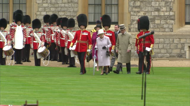 queen elizabeth ii presents new colours to coldstream guards at windsor exterior shots of royal standard flag flying in grey sky and windsor castle... - honour guard stock videos & royalty-free footage